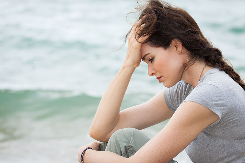 Woman sitting on the beach with her head in her hands, looking sad.