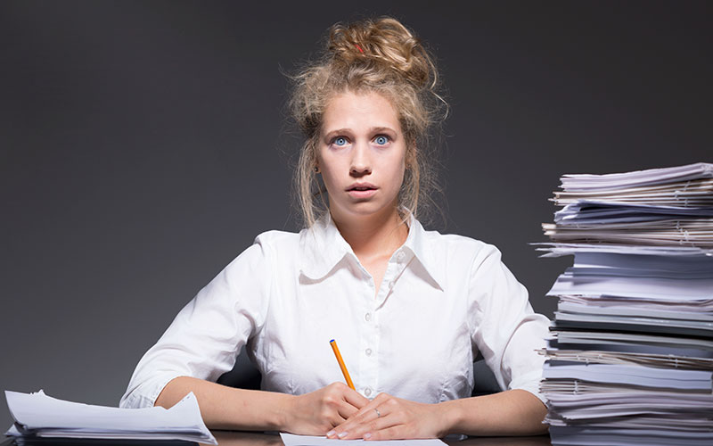 A frazzled female graduate student experiencing burnout sitting at a desk with piles of paper.
