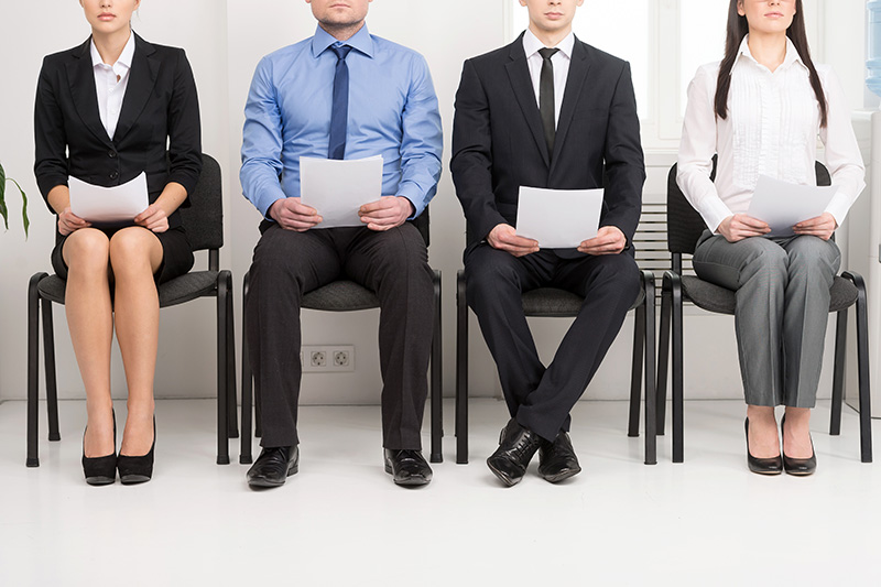 Internship applicants sitting on chairs with their resumes waiting for their interviews.