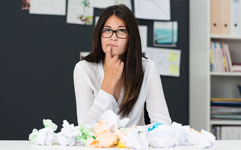 Woman with glasses thinking while surrounded by crumpled paper.