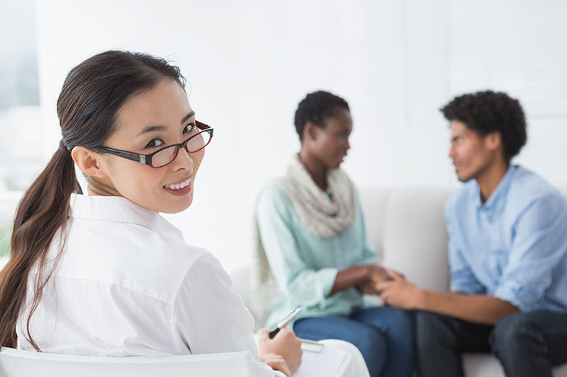 A clinical psychologist works in therapy with a couple.