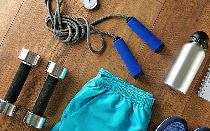 A group of exercise equipment laid out on the floor including hand weights, a jump rope, shorts, and a water bottle.