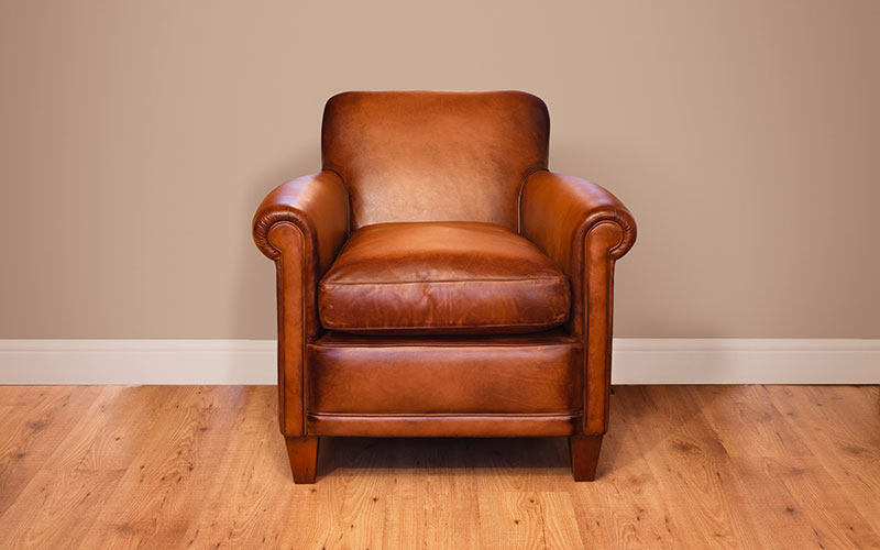 An empty leather armchair in an empty room.