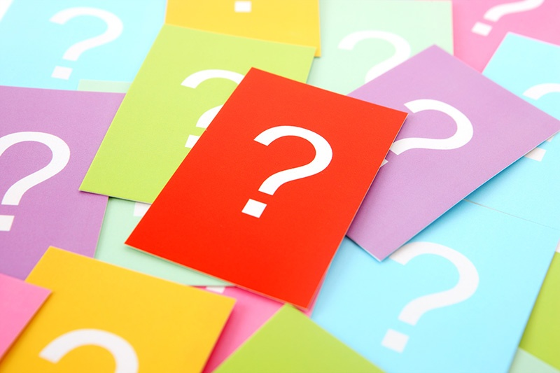 A stack of brightly-colored notecards with a question mark on each one.