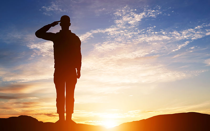 A man in the military saluting in front of a sunset.