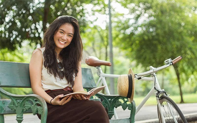 Female grad student sitting on a park bench beside her bicycle smiling and reading a book.