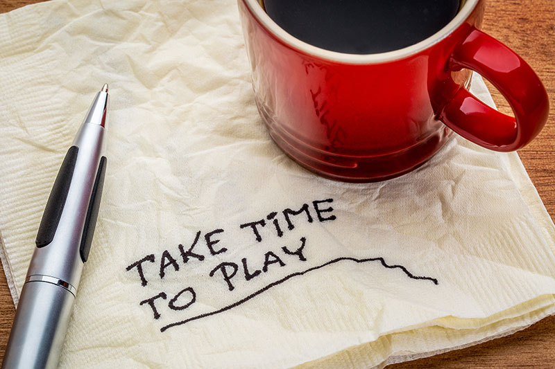 "A cup of coffee on a napkin, on which is written ""Take Time to Play""."