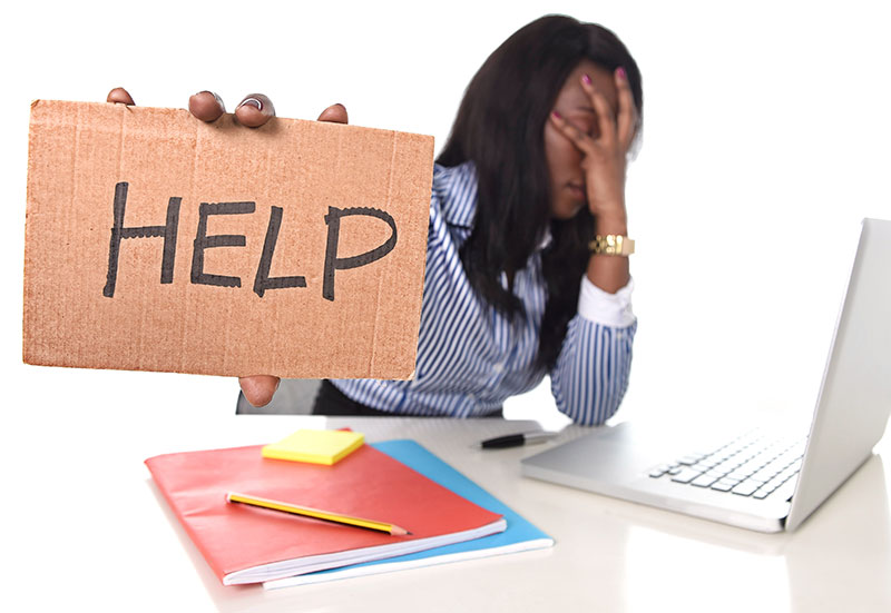 "Female psychology graduate student sitting at a desk with her laptop, her head in her hands and holding up a ""help"" sign."