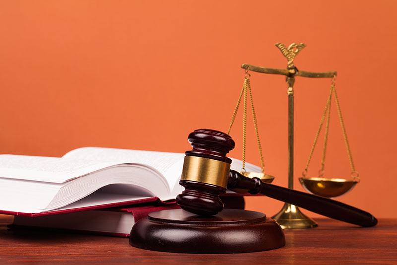 A law book sitting on a desk with scales and a gavel.