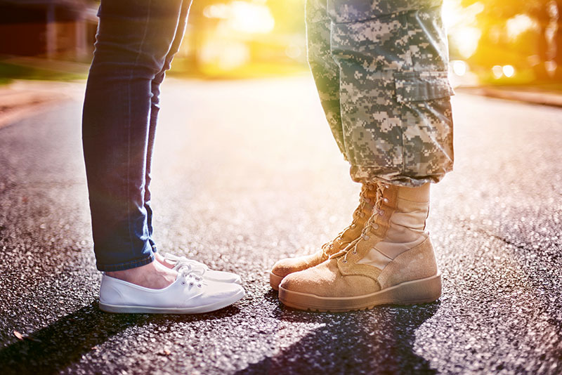 The feet of a soldier and his wife with the sun shining in the background.