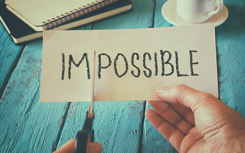 "A piece of paper with the word ""impossible"" with the ""im"" being cut off by a pair of scissors."