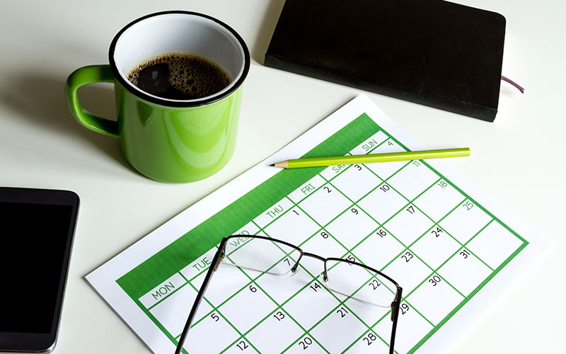 A calendar with coffee, glasses, and a smartphone.