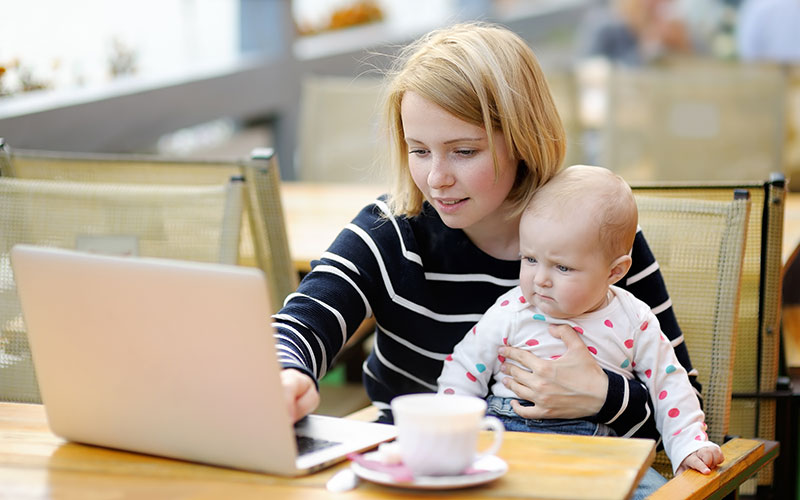 A female grad student who is a parent holding her baby while working on a laptop.